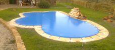 Lona piscina con forma en cesped